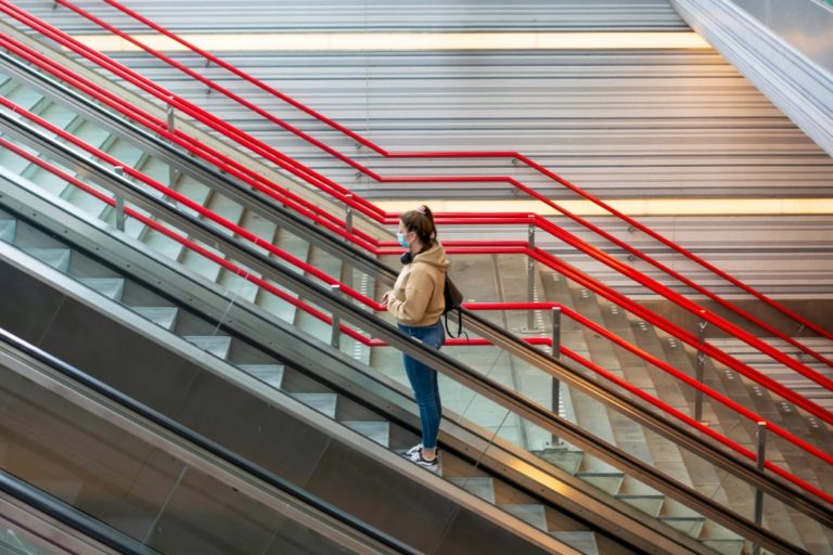 a-young-woman-wearing-protective-face-mask-and-standing-on-escalator-in-railway-station-during_t20_e93QXK